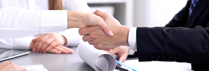 Photo of a chiropractor shaking hands after signing a new clinic contract